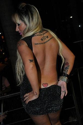 9.jan.2013 - Desinibida, a modelo Sabrina Boing Boing abaixou parte do vestido para mostrar a tatuagem - um coração - que tem no cóccix durante a festa da revista
