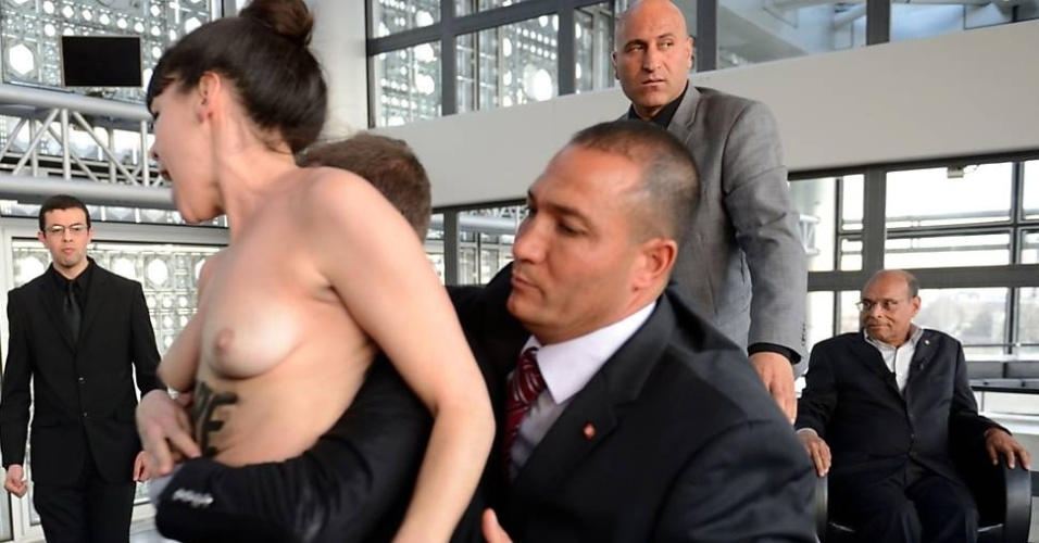 12.abr.2013 - Segurança detém ativista do Femen em protesto contra o presidente da Tunísia, Moncef Marzouki, que está em Paris