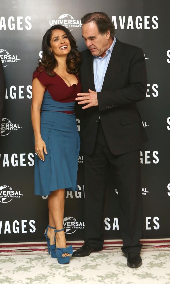 """O decote de Salma Hayek chamou atenção do diretor Oliver Stone durante sessão de fotos de divulgação do filme """"Selvagens"""" em Londres (19/9/12). O cineasta ficou tão empolgado com a imagem de fartura que quase tocou os seios da bela"""